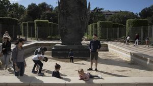 Unos niños juegan ante el TuróPark de Barcelona.