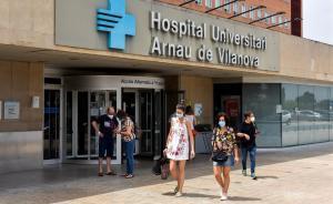 Gente con mascarilla sale del Hospital Arnau de Vilanova, en Lleida.