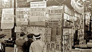 Lectura de diarios y revistas en un quiosco de las Ramblas hace un siglo.
