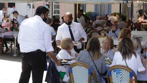 Camareros atienden a clientes en un restaurante de la Barceloneta, en junio pasado.