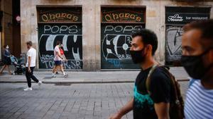 Consumo regulará los requisitos que debe cumplir una mascarilla higiénica. En la foto, dos hombres con mascarilla pasean por el centro de Barcelona, con los comercios cerrados.