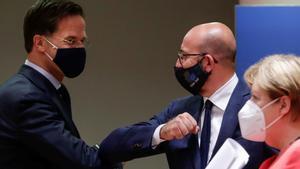 La UE alcanza un acuerdo para salir de la crisis del coronavirus. En la foto,Mark Rutte y Charles Michel se saludan ante Angela Merkel, tras el acuerdo, al final de la cumbre.