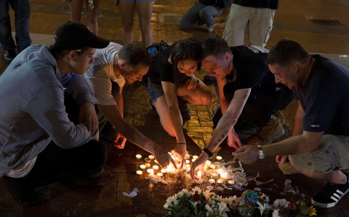 TKX01. Charlottesville (United States), 13/08/2017.- People place candles as they gather during a vigil in Charlottesville, Virginia, USA, 12 August 2017. According to media reports at least one person was killed and 19 injured after a car hit a crowd of people counter-protesting the 'Unite the Right' rally which was scheduled to take place in Charlottesville on 12 August. At least 15 others were injured in clashes during protests. (Protestas, Estados Unidos) EFE/EPA/TASOS KATOPODIS