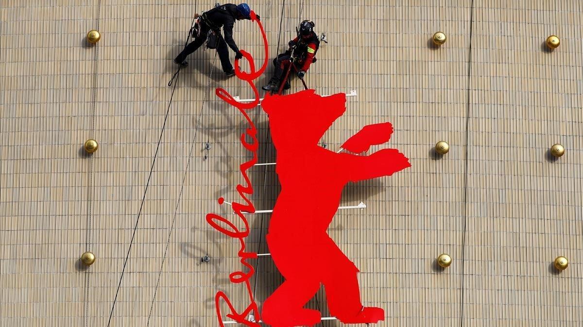 Unos operarios fijan el logo de la Berlinale en el cine Zoo Plast, una de las sedes del festival de Berlín, este miécoles.