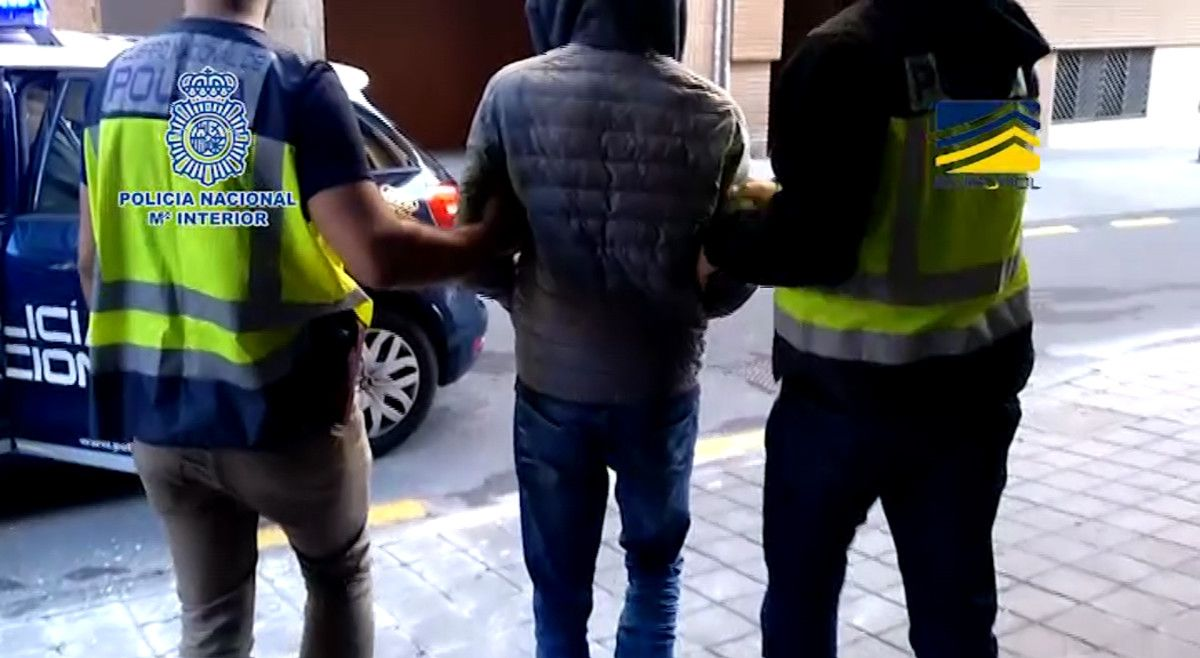 El ciberatracador Denis K. es conducido por agentes de la Policía Nacional tras su detención el 6 de marzo.