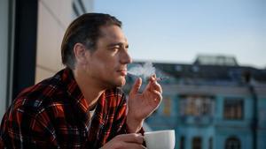 Un hombre fuma en un balcón mientas desayuna.