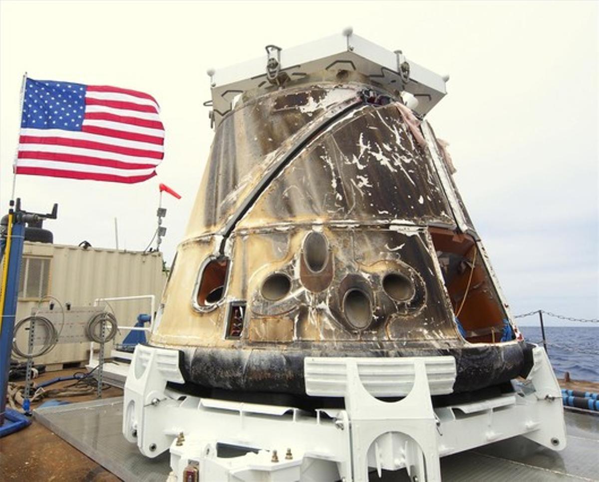 La cápsula espacial 'Dragon', en el barco que la recogió en el Pacífico, cerca de la costa de California, donde amerizó amortiguada por dos paracaídas.