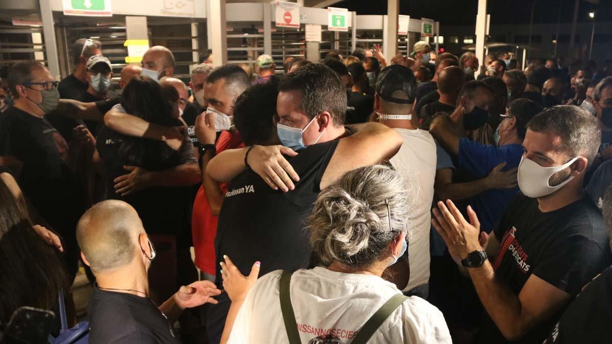 Trabajadores de Nissan se abrazan después del acuerdo alcanzado entre sindicatos y empresa.