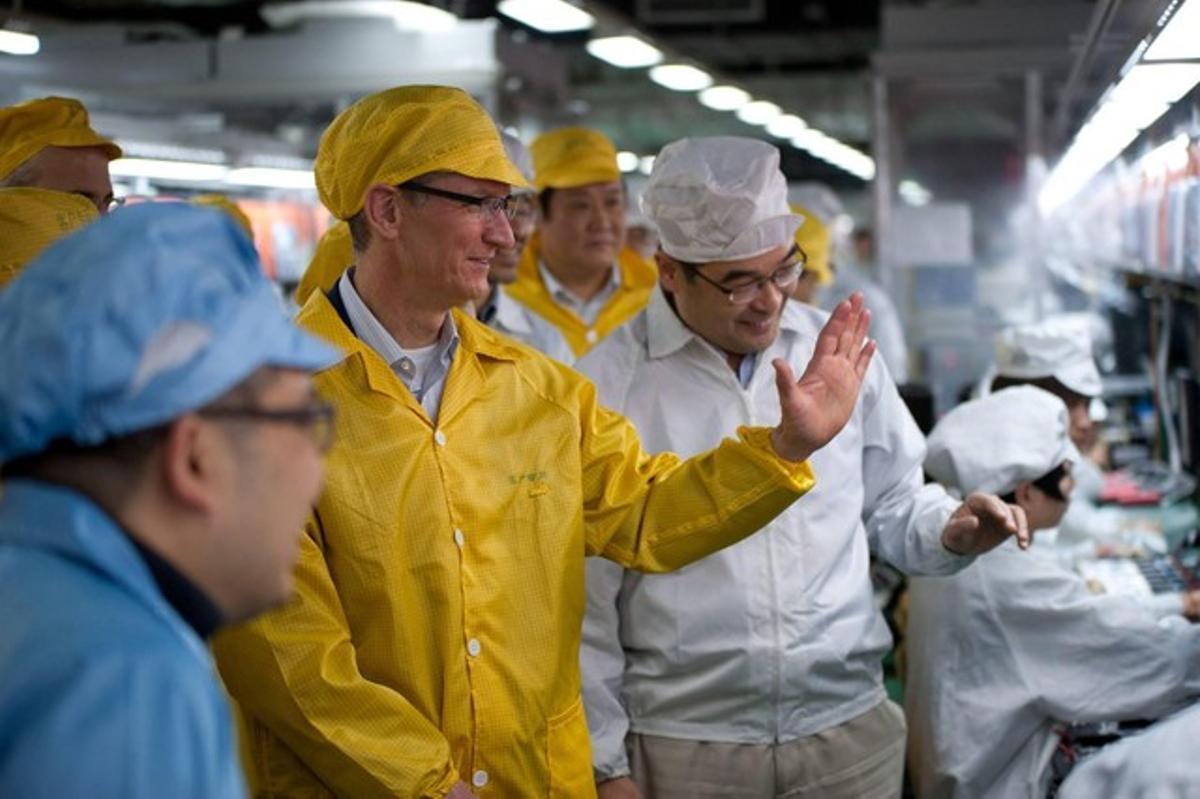 Tim Cook (en primer término, de amarillo), consejero delegado de Apple, durante una visita a una factoría de Foxconn en Henan (China), el pasado marzo.