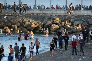 Personas migrantes caminan por la playa del Tarajal, en Ceuta, el pasado 17 de mayo de 2021.
