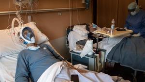 Un paciente con covid lleva una máscara de buceo integral en el Hospital Maria Pia de Turín, el pasado 7 de abril, mientras su compañero de habitación está siendo atendido por un sanitario.
