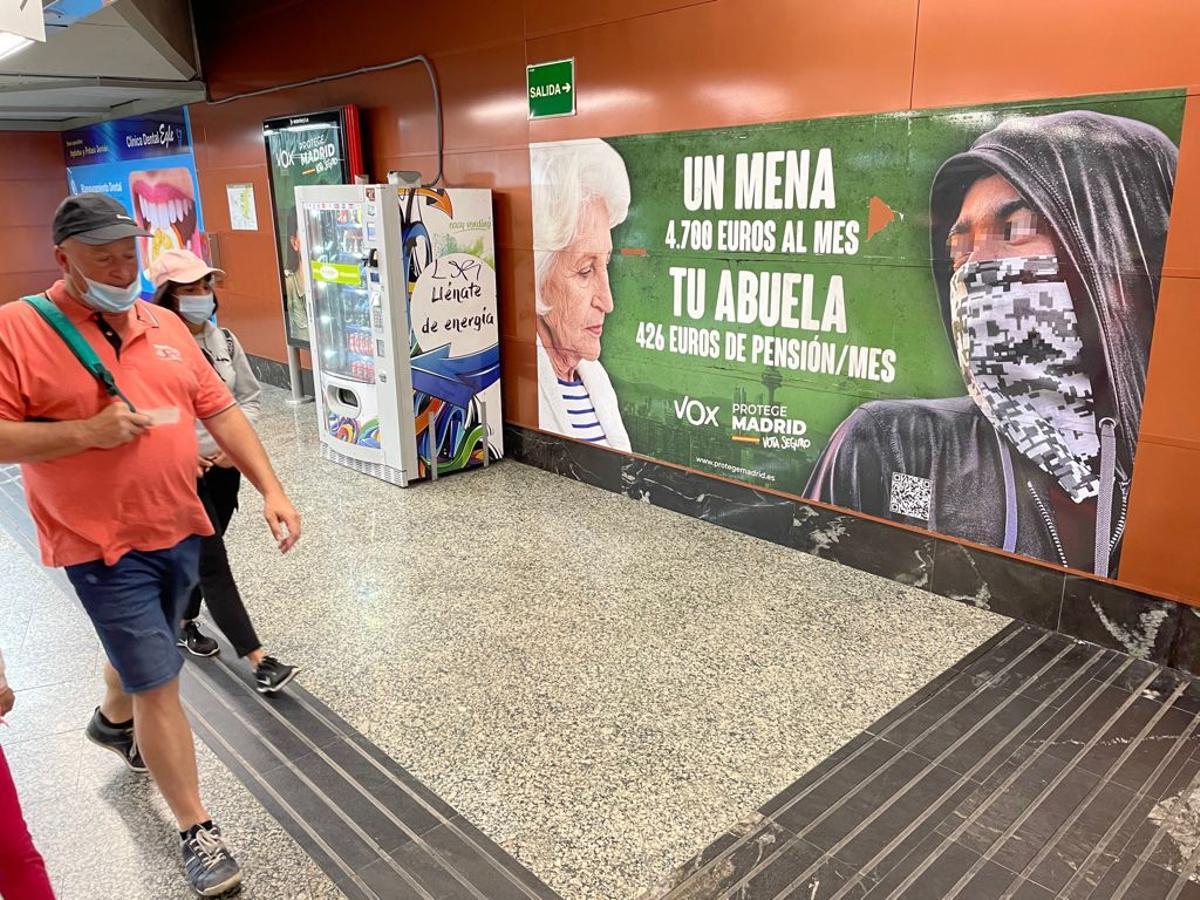 Usuarios del Metro y de Cercanías pasan junto al cartel electoral contra los menores no acompañados que ha instalado Vox en la estación madrileña de la Puerta del Sol.