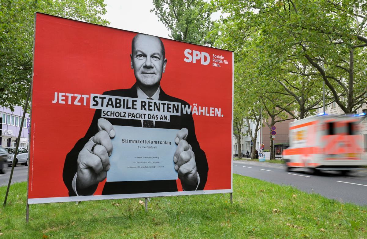 Un coche pasa frente a un cartel electoral del candidato socialdemócrata, Olaf Scholz, que anima a los votantes a emitir el voto por correo.