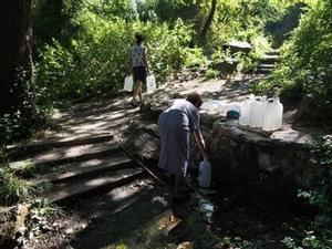 La gent s'acosta a omplir garrafes amb aigua de la font d'en Vinyes.