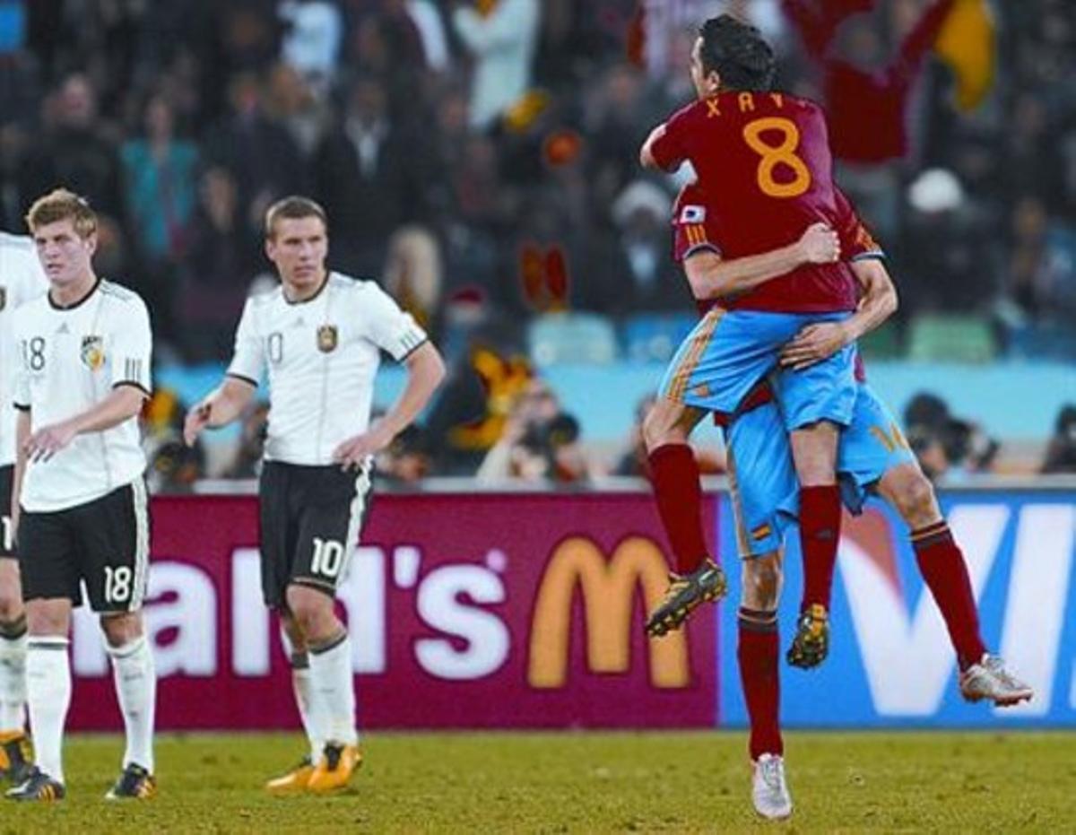 Xabi y Busquets se abrazan tras el gol ante la decepción de los jugadores alemanes.