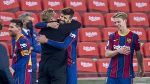 Koeman se abraza con Piqué tras remontar al Sevilla y pasar a la final de la Copa.