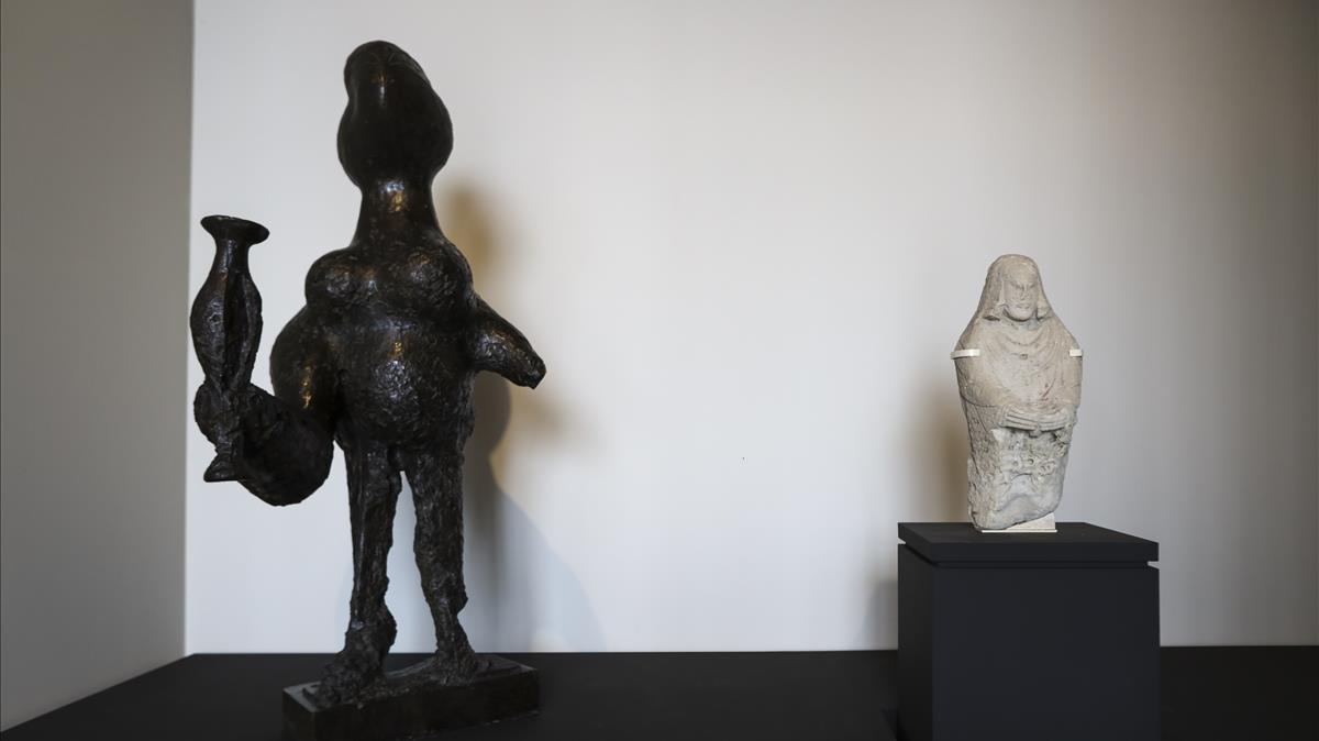 La escultura 'Femme au vase' de Picasso, junto a una pieza de mujer oferente del periodo ibero encontrada en el Cerro de los Santos, en la exposición 'Picasso ibero' de Santander.