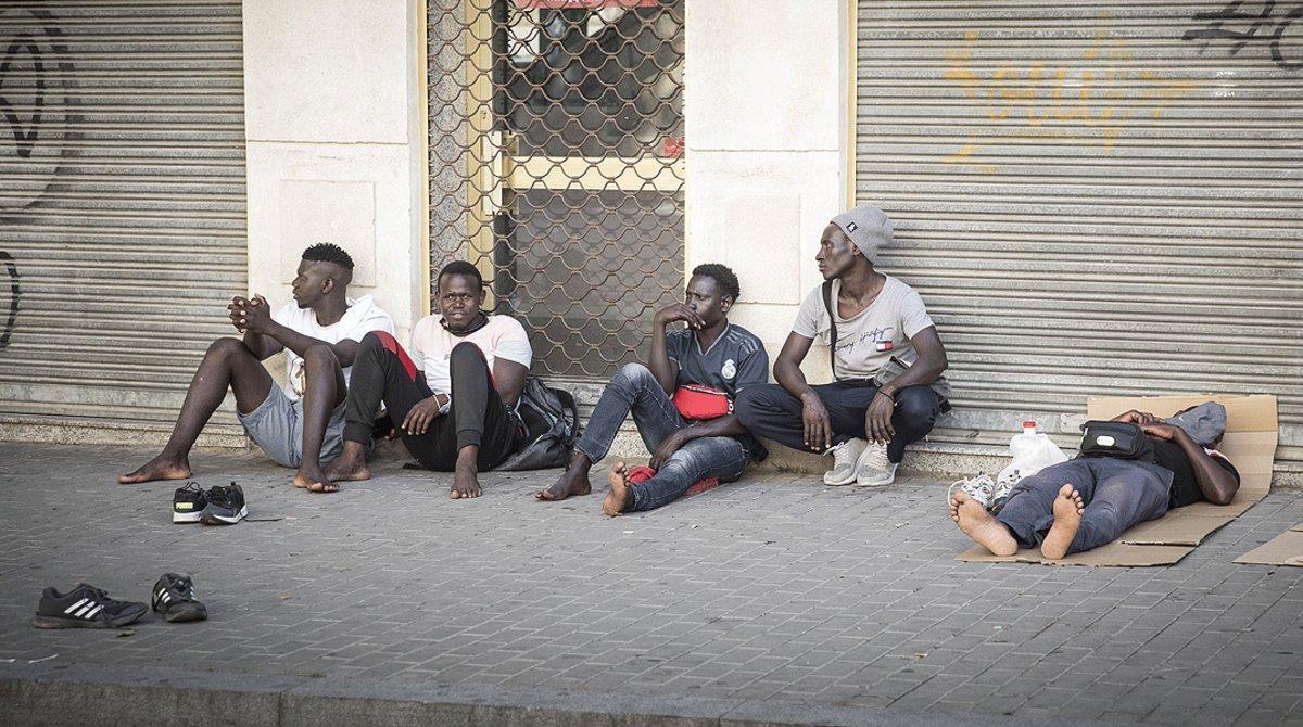 Varios temporeros sin trabajo descansan en plena calle, el 3 de julio en Lleida.