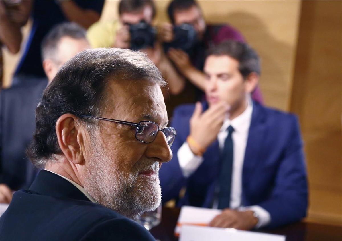 El presidente del Gobierno en funciones y líder del PP, Mariano Rajoy, en la firma del pacto de investidura con el jefe de Ciudadanos, Albert Rivera.
