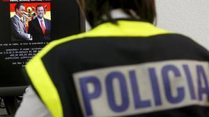 Un agente de la Policia Nacional examina el ordenador de un hacker que habíaatacado paginas web de empresas de telefonia y sitios gubernamentales de Estados Unidos, Latinoamerica y Asia.