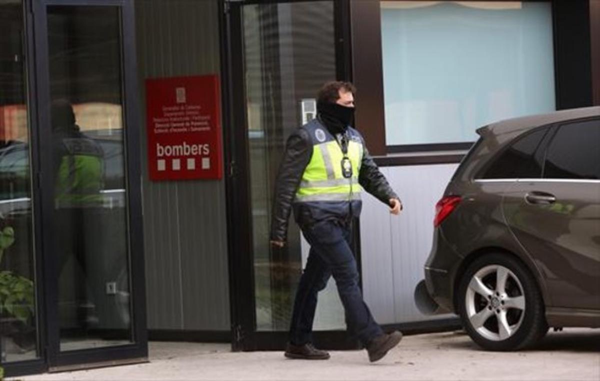 Un policía sale de la sede de los bomberos de Sant Boi, mientras se procedía al registro, ayer.