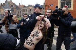 La policía francesa se lleva a rastras a una de las activistas de Femen que ha asaltado el vehículo de Strauss-Khan a su llegada al juzgado, este martes.