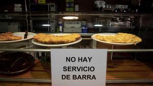 Un cartel en un bar de València indica la prohibición de consumir en la barra por el coronavirus.