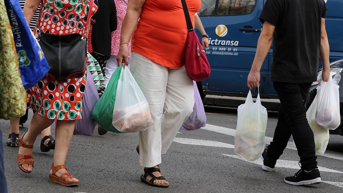 Consumidores con bolsas de plástico de asas.
