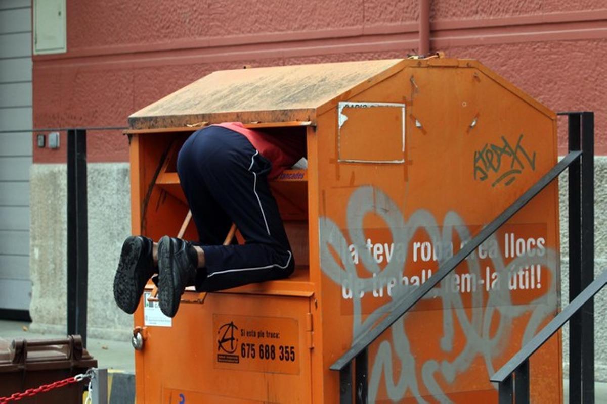 Un hombre rebusca dentro del contenedor de una oenegé.