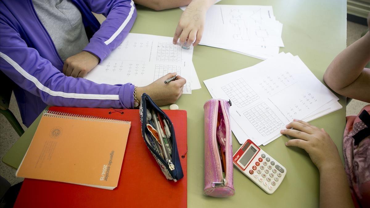 Unos estudiantes hacen deberes en la biblioteca de su colegio.