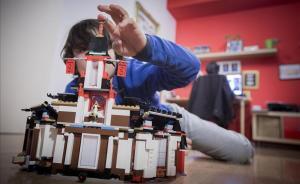 Un niño haciendo una construcción en el salón de su casa.