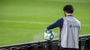 Un recogepelotas desinfecta el balón en el Camp Nou.