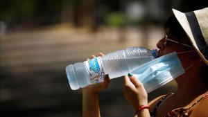Una mujer bebe agua para aliviar las altas temperaturas, en Córdoba.