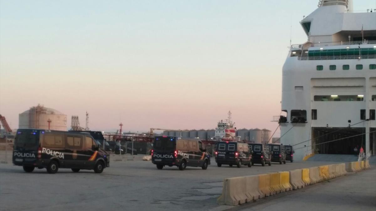 Furgones de la Policía Nacionalentranen uno de los barcosatracados en el Port de Barcelona.
