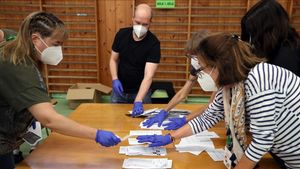 El presidente y los miembros de una mesa electoral hacen el recuento de votos en Bilbao, tras el cierre de los colegios electorales, este domingo.
