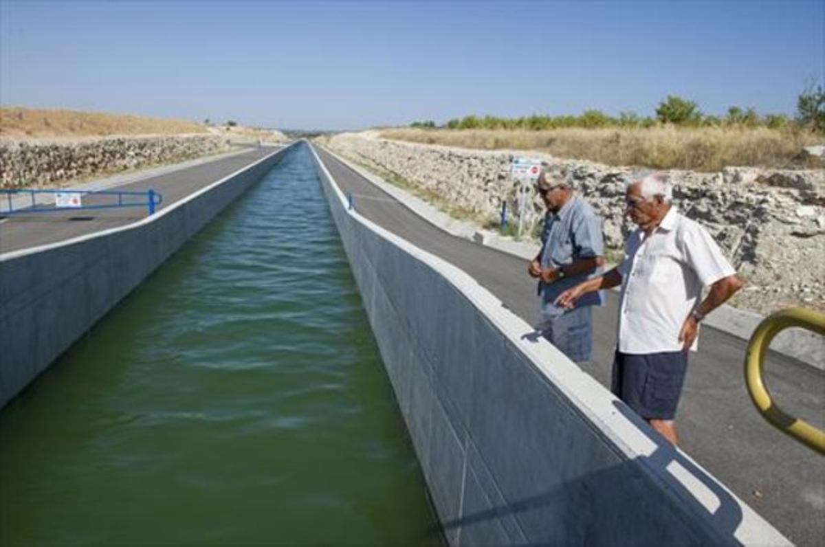 Dos vecinos de la zona contemplan el paso del agua por el Segarra-Garrigues, cerca de Les Borges, ayer.