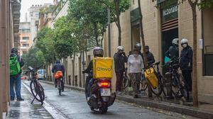 Un grupo de 'riders' esperan para recoger pedidos ante un establecimiento de comida rápida de Gràcia, el 14 de mayo.