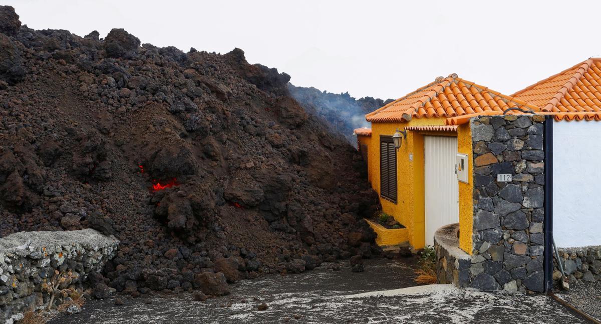 Desde Tajuya, en El Paso, se observa claramente la erupción y cómo corre la lava por una ladera que está siendo transformada por el material volcánico que no para de emerger por el cono del volcán.