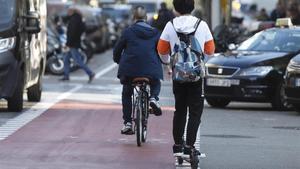 Un joven circula en patinete eléctrico por el carril bici de carrer Provença, en Barcelona.