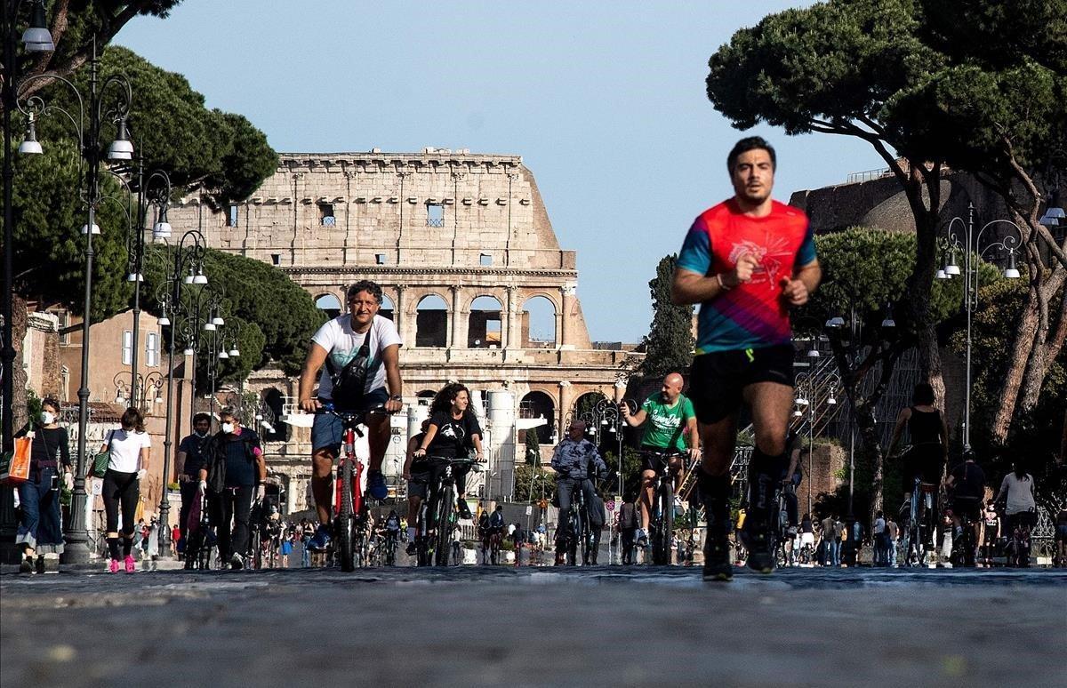 La gente pasea y practica deporte tras la suavización del confinamiento alo largo de Via dei Fori Imperiali.
