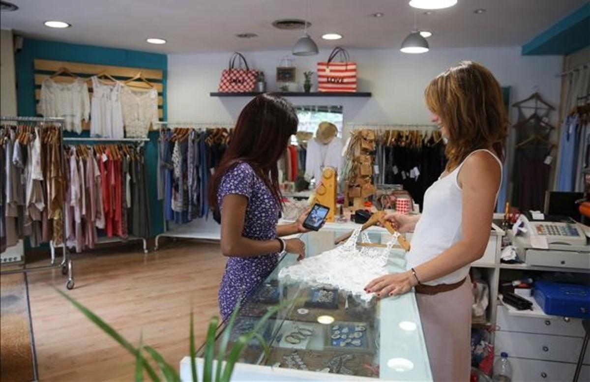 Una clienta busca en la tienda Friends del Eixampleuna prenda que ha visto expuesta desde la app de Yuge en su móvil.
