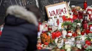 Una mujer deposita flores en el homenaje de Trier.