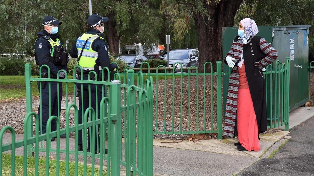 Un policía atiende a una mujer en un puesto de control en Melbourne.