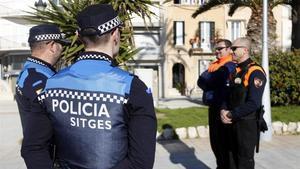 Dos agentes de la Policía Local de Sitges acompañados de vigilantes de seguridad privada.