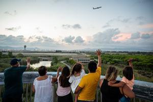 Una familia despide a un avión que despega en el aeropuerto de Barcelona.