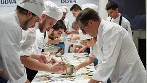 Andrea Caiazzo y Josep Queralt preparan un plato con Joan Roca.