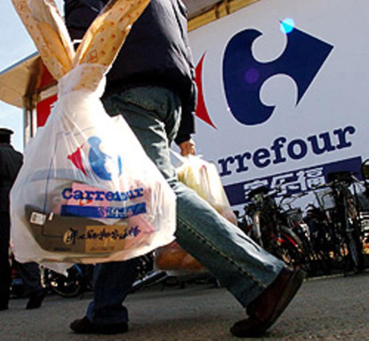 Un cliente abandona un centro Carrefour tras realizar sus compras.