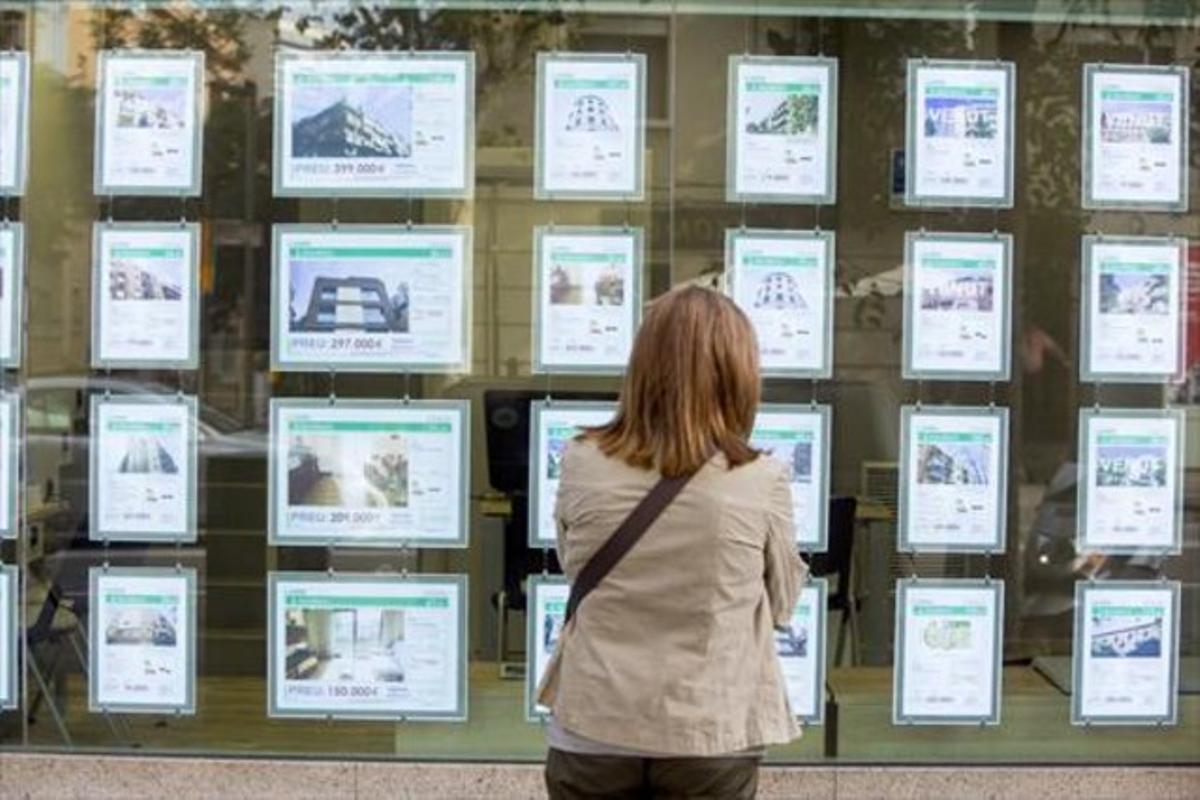 Una viandante observa anuncios de pisos en una inmobiliaria de Barcelona.