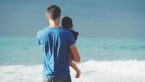 Padre con su hijo mirando al mar.