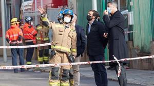 Pablo Casado y Xavier García Albiol atienden las explicaciones de un bombero frente a la nave incendiada en Badalona.